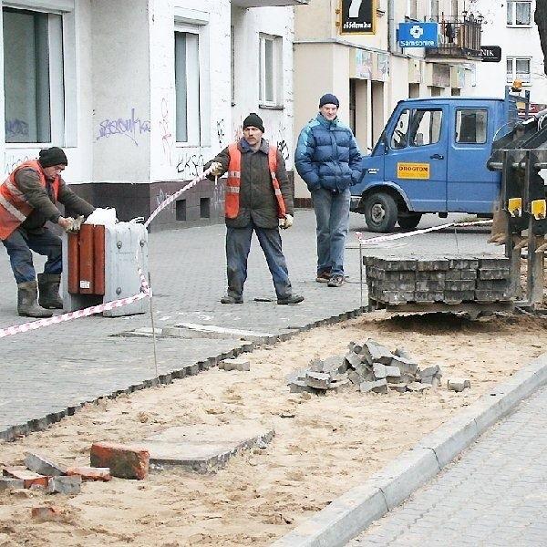 """Pracownicy """"Drogtomu"""" układają kostkę  polbrukową na chodnikach i zatoczkach  autobusowych"""