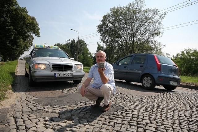 Waldemar Rzucidło demonstruje kostkę, którą po porstu można wyjść z rozjeżdżonej ulicy Kostrzyńskiej