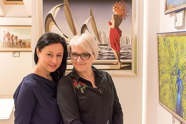 """Małgorzata Ziewiecka, pomysłodawczyni wystawy """"Metamorfozy"""" (z prawej) w Radomiu na tle obrazów z wystawy z Marilą Kończak, artystką."""