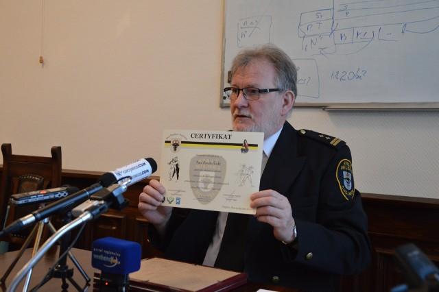 Komendant Arkadiusz Megger prezentuje certyfikat, który zdobyły panie uczestniczące w kursie samoobrony.