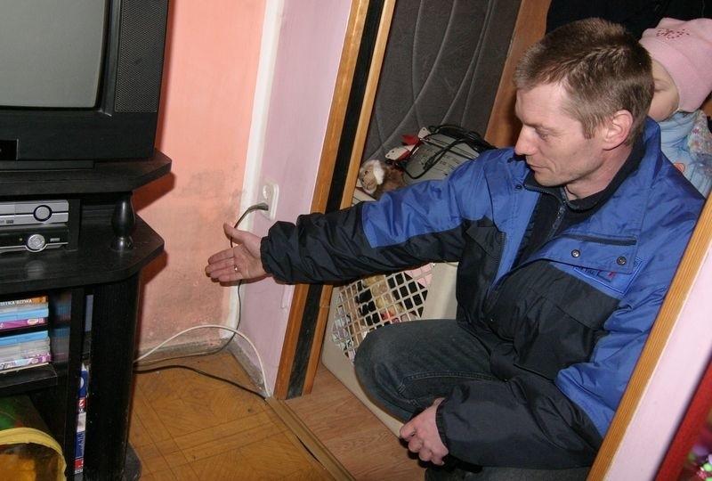 Marek Łasica pokazuje wilgoć na ścianie w swoim mieszkaniu.