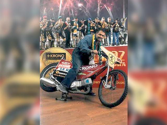 Piotr Pietrasiak na motocyklu stojącym w  SWISS KRONO. Kiedyś żużlowy kącik miał też  zdjęcie kibiców Falubazu