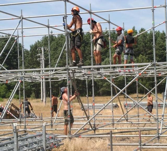 Na polu, gdzie już za nieco ponad dwa tygodnie odbędzie się Przystanek Wodostock, już trwają pierwsze prace. Na zdjęciu robotnicy montują scenę.