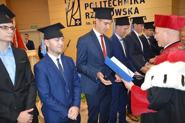 Prorektor profesor Jarosław Sęp wręcza absolwentom dyplomy ukończenia studiów inżynierskich