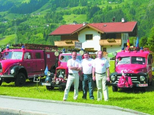 O lewej Mirosław Bałło, Jerzy Szymański z OSP Orla oraz st. bryg. Jan Bartoszuk na tle zabytkowych pojazdów pożarniczych