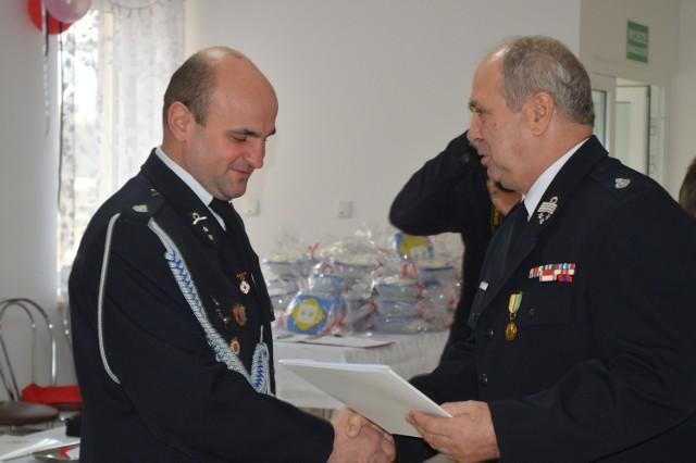 Bartłomiej Hryńczuk odbiera nagrodę z rąk wójta, Ryszarda Klisowskiego