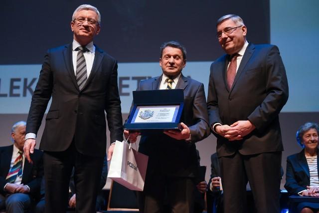 Włodzimierz Kotliński odbiera nagrodę Superseniora z rąk prezydenta Poznania, Jacka Jaśkowiaka i przewodniczącego Rady Miasta Poznania, Grzegorza Ganowicza
