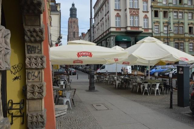 Kelnerzy rozstawiają parasole, stoliki i krzesła przed wrocławskimi lokalami