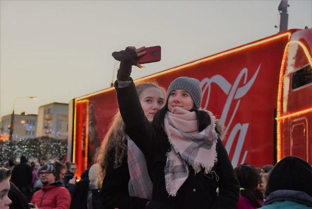 """W piątek, 8 grudnia, na Starym Rynku przy katedrze zaparkowała wielka, długa na kilkanaście metrów ciężarówka Coca-Coli. A jeszcze dłuższa od samej ciężarówki była... kolejka gorzowian stojących po stworzenie wyjątkowej, spersonalizowanej puszki z napojem. Impreza rozpoczęła się oficjalnie o godz. 15.00. Ale oficjalnie! Pierwsi mieszkańcy na miejscu zjawili się już godzinę wcześniej, a wszystko po to, by mieć szansę na skorzystanie ze wszystkich atrakcji przygotowanych przez Coca-Colę. A było ich całkiem sporo! Oprócz możliwości wyrobienia puszki ze swoim imieniem - albo imieniem kogoś bliskiego - można było też zrobić sobie fotkę z Mikołajem, stworzyć świąteczne dekoracje oraz zgarnąć darmowy napój. Aby dostać darmową colę, należało zrobić sobie zdjęcie podczas imprezy i wrzucić je na Facebooka lub Instagram i opatrzyć hashtagiem (# - znakiem) z dopiskiem """"dziekuje"""". Zrobienie zdjęcia w tym miejscu nie było niczym trudnym, bo Coca-Cola rozstawiła też na Starym Rynku kilka podestów, z których łatwiej było zrobić sobie selfie z wielką ciężarówką w tle. Gorzowianie w oczekiwaniu na atrakcje byli cierpliwi, chociaż na dworze gorąco już nie jest... - Jest świąteczna muzyka, dużo osób, wesoła atmosfera... Czas fajnie płynie! - skomentowała Joanna Papis. Najbardziej zadowolone były dzieci. - Zrobiłem swoją puszkę Coca-Coli! Warto było tyle czekać. Jedną mam ze swoim imieniem, a drugą zrobiłem z imieniem mamy - mówił Gracjan z Gorzowa. Zobacz też: Magazyn Informacyjny """"GL"""""""