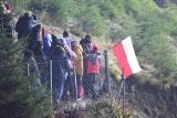 Skoki narciarskie w Wiśle. Ludzie kibicują zawodnikom zza ogrodzenia. Policja ostrzega przed mandatami