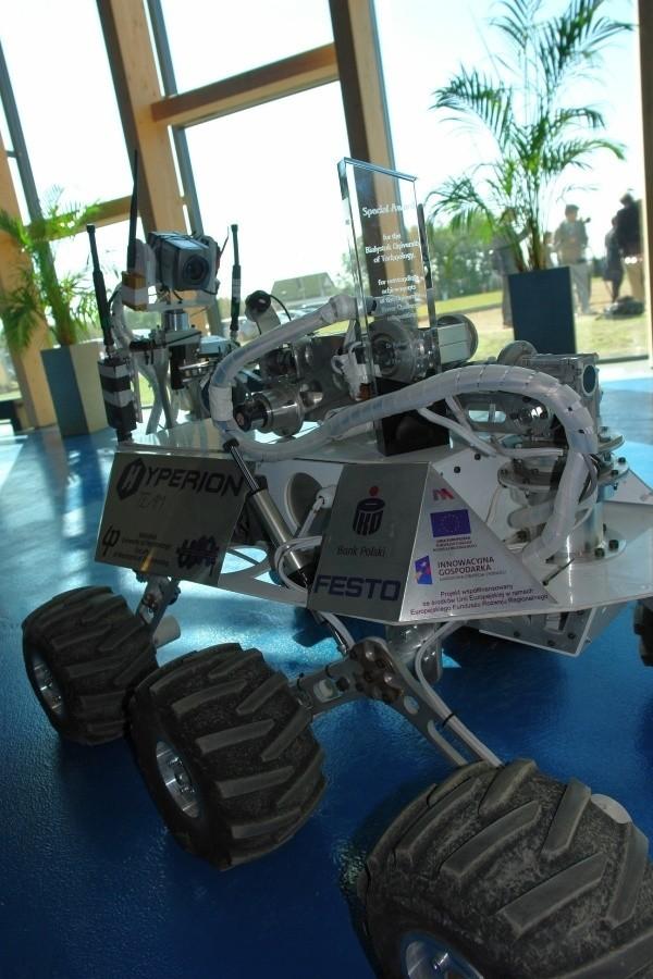 """Michał Grześ i łazik HYPERION 2 uczestniczą w trzydniowej konferencji  """"Człowiek w Kosmosie"""". Wśród prelegentów są m.in. Scott Hubbard z NASA, który doprowadził do lądowania na """"czerwonej planecie"""" pierwszej sondy kosmicznej Pathfinder. Konferencja przeznaczona dla znawców i pasjonatów tematyki kosmicznej odbywa się w  Regionalnym Centrum Naukowo-Technologicznym w Podzamczu."""