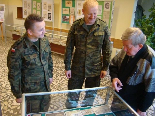 Oprawej - autor wystawy, Tadeusz Konieczka, mjr Artur Wiśniewski i kpt. Sylwester Ludwiczak nad gablotą zawierającą pamiątki numizmatyczne.