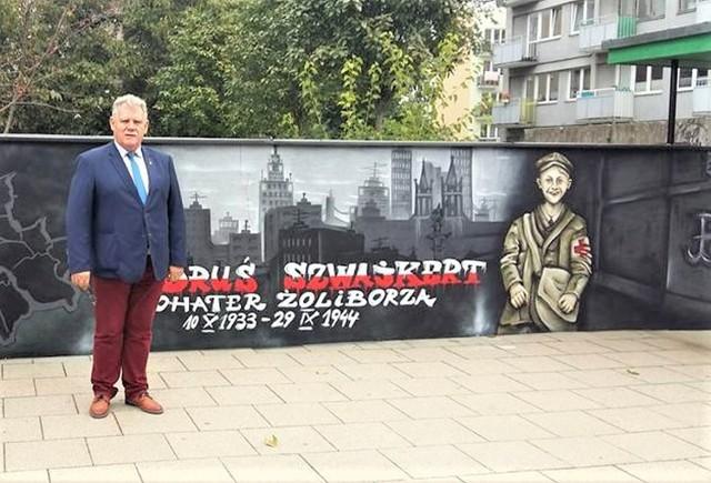 Radny Kaczmarek przy muralu poświęconym Jędrkowi Szwajkertowi na terenie warszawskiej podstawówki