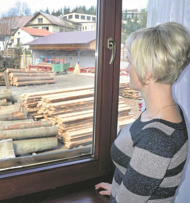 Bożena Pachura przy oknie z widokiem na tartak