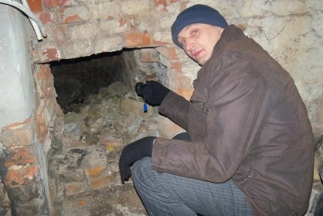 Alfred Tomanek, pracownik urzędu miejskiego w Głogówku, pokazuje wejście do tajemniczych podziemi. Od czasu ich odkrycia przy przebudowie centralnego ogrzewania, nikt nie zapuszczał się do środka.