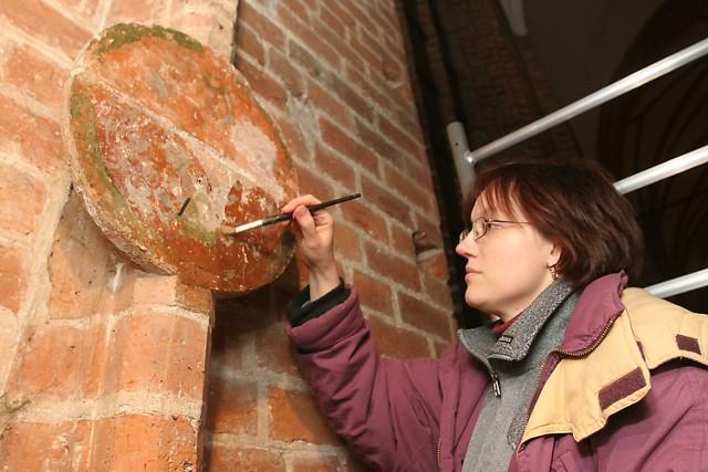 Lidia Piotrowska-Cześnik z pracowni konserwatorskiej Muzeum Narodowego maluje farbami akrylowymi rekonstrukcje herbu rodziny znajdujący się na tarczy, zwanej zacheuszkiem.