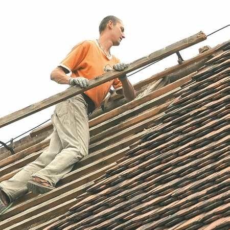 Rafał Michalski ciężko pracuje przy przekładaniu dachu na kościele. - To precyzyjna robota i do tego trzeba być bardzo ostrożnym - mówi.
