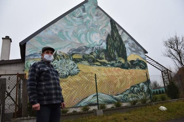 """Sztuka w Brzózkach jest wielka nie tylko dlatego, że murale pokryły szczytowe ściany budynków. Wszak o samego Vincenta van Gogha chodzi. Gdy stowarzyszenie """"Twórcze Brzózki"""" wyszło z inicjatywą upiększenia wsi poprzez sztukę, niektórzy mieszkańcy mówili wprost, że woleliby... drogę. Kiedy usłyszeli, że dotacji na sztukę nie można przesunąć na drogę, zgodzili się. Ustalono, że murale będą inspirowane obrazami holenderskiego malarza. Na razie w Brzózkach murali jest pięć, ale jest jeszcze kilka elewacji, które będzie można upiększyć pejzażami inspirowanymi obrazami van Gogha. Dziś mieszkańcy są dumni z tego co wspólnie udało się stworzyć. Dopełnieniem charakteru wsi są drewniane rzeźby i kapliczki. Rzeźb jest dwadzieścia, kapliczek piętnaście. Powstały podczas plenerów organizowanych przez stowarzyszenie. Ich wieś stała się atrakcją turystyczną, a wielu mieszkańców odnalazło w sobie artystyczną duszę. Tworzą dla siebie i innych. Na zdjęciu: Kazimierz Baumann i mural inspirowany obrazem - """"Pole pszenicy z cyprysami"""""""