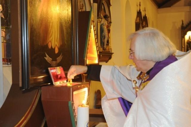 Ks. Marcin Ogiolda umieszcza w bocznym ołtarzu relikwiarz z kroplą krwi bł. Jana Pawła II.