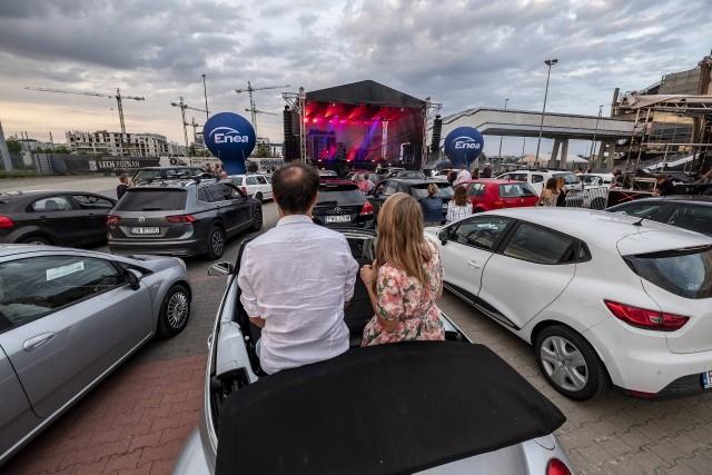 W sobotni wieczór na parkingu przed stadionem w Poznaniu odbył się koncert samochodowy w ramach Enea Edison Festival. Na scenie wystąpił Artur Rojek.- Wydarzenie skrojone zostało wprost pod nową rzeczywistość, w której przyszło się nam odnaleźć. Nasze pragnienie spędzania lata na świeżym powietrzu i wśród ludzi, a z drugiej strony oficjalne zalecenia i rekomendacje rządowe, które od tego odwodzą, musiały zaowocować w końcu pomysłami, które przechytrzą obecną sytuację - tłumaczą organizatorzy.Przejdź dalej i zobacz zdjęcia --->