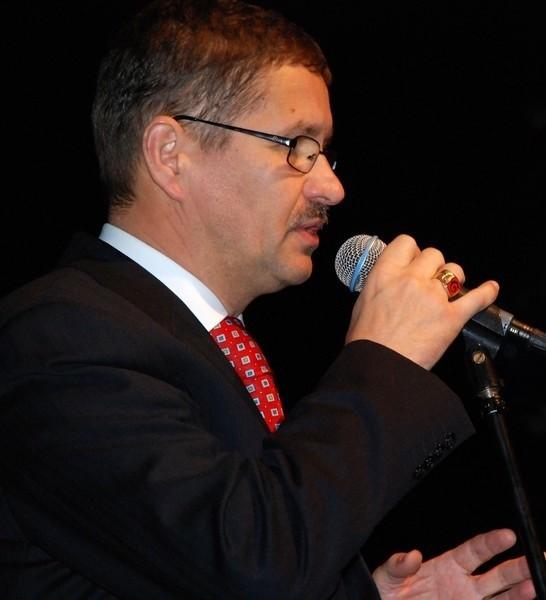 Prezydent Jan Zubowski miał podczas gali ciemny garnitur, czerwony krawat i sygnet. Na czerwonym tle widać literę G