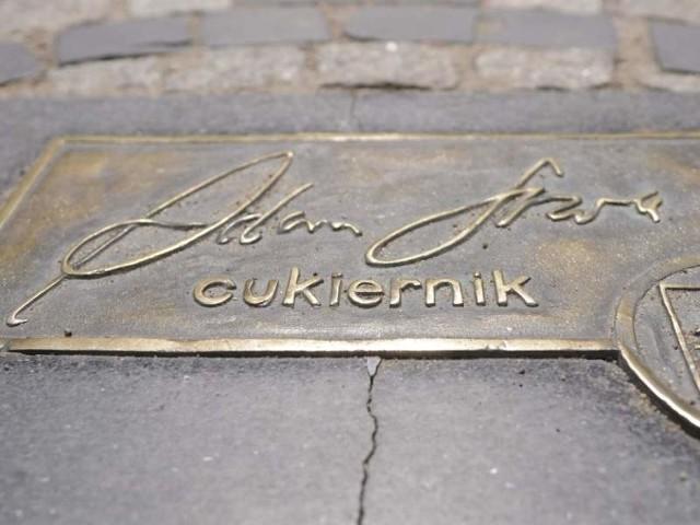 Autograf bydgoskiego cukiernika Adama Sowy. Otaczająca tabliczkę płyta jest pęknięta w dwóch miejscach
