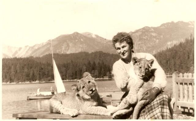 Hermine Braunsteiner pozuje z lwiątkami. W tle widać jezioro Eibsee, u podnóża najwyższego szczytu Niemiec – Zugspitze (1957)