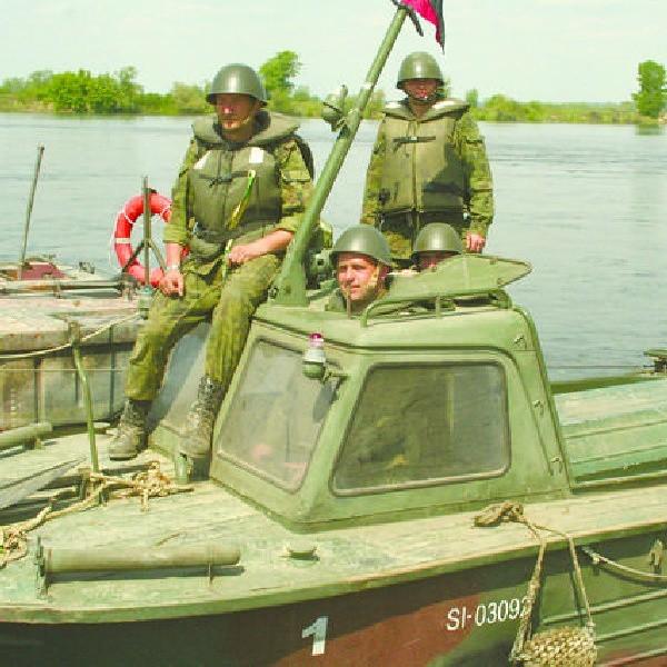 Żołnierze w kutrach podtrzymujących elementy mostu