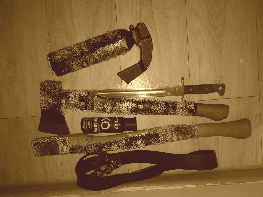 Siekierka, dwa pojemniki z gazem różnej wielkości, maczeta, styl od siekiery, czarny pasek. Przedmioty oklejone naklejkami, zdjęcie wykonane w sepii, naklejki zamazane