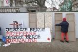 """""""Jeszcze będzie przepięknie, jeszcze będzie normalnie"""". Na placu Wolności grupa młodych osób maluje plakaty"""