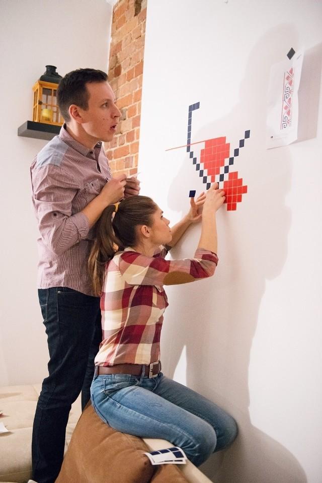 Wzór Ornament z kolekcji FolkWzory Puzzlove to dekoracje składające się z małych samoprzylepnych elementów. Kwadratowe dekoracje można zamontować samemu i bardzo dobrze się przy tym bawiąc. W zestawie jest komplet potrzebnych do wyklejenia grafiki kwadratów oraz instrukcja, ułatwiająca prawidłowe naniesienie dekoracji na powierzchnię.