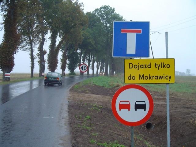 Droga z Kamienia do Świerzna. Zakaz wjazdu i informacja, że droga prowadzi jedynie do Mokrawicy. Kierowca ma do wyboru: cofnąć się do objazdu lub - mimo wszystko - próbować przejechać.