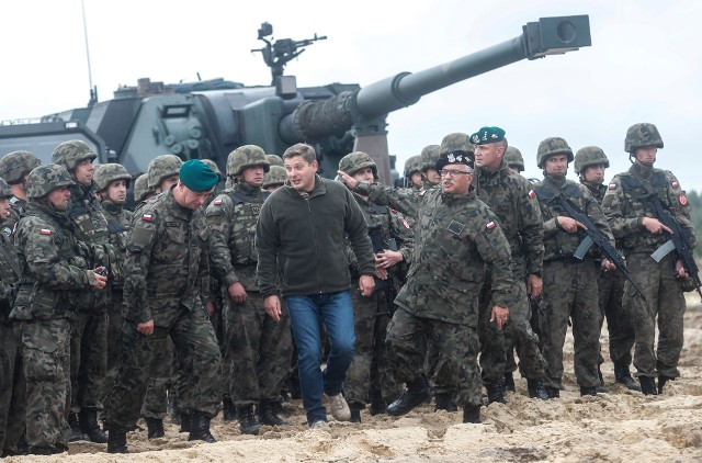 """Ośrodek Szkolenia Poligonowego Wojsk Lądowych w Nowej Dębie przypominał prawdziwe pole walki. Można było tam zobaczyć ciężki sprzęt wojskowy typu: transportery """"Rosomak"""" w różnych wersjach, samobieżny moździerz """"Rak"""", armatohaubice """"Krab"""", Radiolokacyjny Zespół Rozpoznania Artyleryjskiego """"Liwiec"""", czołg PT-91, Leopard 2A5 czy sprzęt przeciwlotniczy. Każdy mógł go dotknąć czy wejść do środka. Łącznie zaprezentowano ponad 30 egzemplarzy nowoczesnego sprzętu militarnego wyprodukowanego przez Polską Grupę Zbrojeniową. Był to wstęp do rozpoczynających się kieleckich targów XXV MSPO. - W ten sposób chcieliśmy naszym zagranicznym gościom: z Korei, Pakistanu, Węgier czy Estonii pokazać potencjał polskiego przemysłu. """"Raki"""", które doskonale się tutaj zaprezentowały to sprzęt, który do wyposażenie polskiej armii trafił dwa miesiące temu, a który produkowany jest niedaleko, bo w Hucie Stalowa Wola. Widzę, że cieszy się on ogromnym zainteresowaniem m.in. delegacji Koreańskiej - mówił wczoraj sekretarz stanu w Ministerstwie Obrony Narodowej Bartosz Kownacki. - Mam nadzieję, że dzisiejsze spotkanie przyczyni się do tego, że w przyszłości pojawią się nowe kontrakty dla polskiego przemysłu zbrojeniowego - dodał. Zaproszeni goście mieli także okazję zobaczyć ciężki sprzęt w akcji. Przed wieżą na bojowej strzelnicy artylerii odbyły się ćwiczenia taktyczne. Strzelały """"Raki"""", """"Kraby"""", które jednocześnie wykonywały zasłony dymne, słychać było wybuchy, a w powietrzu unosił się dym. Pod koniec pojawiły się śmigłowce. Wodegraniu scenki niczym z wojennego filmu wzięło udział kilka jednostek Sił Lądowych Wojska Polskiego - Była to przede wszystkim 21 Brygada Strzelców Podhalańskich, 17 Brygada Zmechanizowana, 11 Pułk Pancerny z Bartoszyc, 1 Brygada Lotnictwa Wojsk Lądowych i 25 Brygada Kawalerii Powietrznej - wymienia oficer prasowy 21 Brygady Strzelców Podhalańskich. Kownacki o Autosanie: Niech wyciągną wnioski W czasie spotkania z dziennikarzami sekretarz stanu w Ministerstwie Obrony Naro"""
