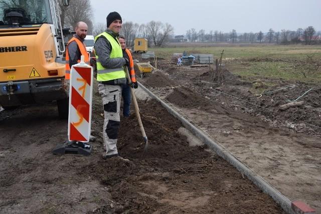 """Rozpoczęły się roboty przy budowie dawno zapowiadanej ścieżki rowerowej na trasie Kupienino - Ojerzyce - Szczaniec. Zakres robót obejmuje odcinek od przejazdu kolejowego w Kupieninie do wiaduktu kolejowego w Szczańcu, o długości 4,5 km. Nawierzchnia ścieżki wyłożona zostanie betonową kostką typu polbruk w kolorze czerwonym i szarym, podobnie jak na odcinku Szczaniec - Myszęcin. Gmina zleciła inwestycję w formule """"zaprojektuj - wybuduj"""", wykonawca robót opracował dokumentację, uzyskał wymagane zgody, a starosta świebodziński wydał zgodę na prowadzenie robót. Rowerem po nowej ścieżce będzie można przejechać już we wrześniu, kiedy to odbywa się coroczny rajd rowerowy szlakiem Pętli A2, zapewne trasa zostanie przedłużona, z metą w Ojerzycach.Zobacz też: II Rodzinny Rajd Rowerowy w Szczańcu"""