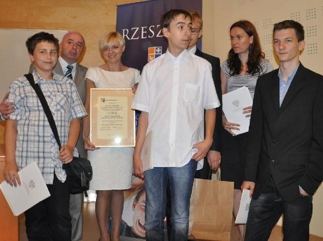Uczniowie Zespołu Szkół Społecznych numer 2 w Tarnobrzegu wraz z dyrektor Anitą Woźniak (trzecia z lewej) oraz podkarpackim kuratorem oświaty Jackiem Wojtasem (drugi z lewej) podczas gali wręczania nagród dla olimpijczyków.