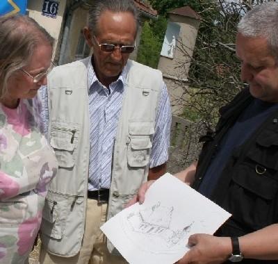 Przemysław Karwowski pokazuje Genowefie i Wiesławowi Piotrowskim, gdzie przed 200 laty stała kapliczka św. Mikołaja: przed budynkiem, którego jeszcze nie było i którego za chwilę nie będzie...