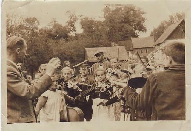 Dzieci ze szkolnego zespołu muzycznego wraz z kierownikiem Józefem Lachnerem (który kierował placówką do 1972) i Franciszkiem Szumcem późniejszym dyrektorem szkoły na obecnym boisku. W tle zabudowania dawnej szkoły i szpitala oraz karczmy w Modlnicy