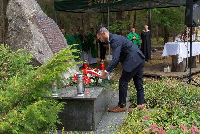 Wójt Pysznicy Łukasz Bajgierowicz składa wieniec na obelisku z nazwiskami pomordowanych