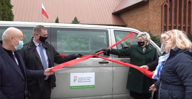 Samorządowcy oraz zaproszeni goście odsłaniają nowoczesny samochód, który będzie służył do przewozu niepełnosprawnych podopiecznych Warsztatu Terapii Zajęciowej w Grójcu.