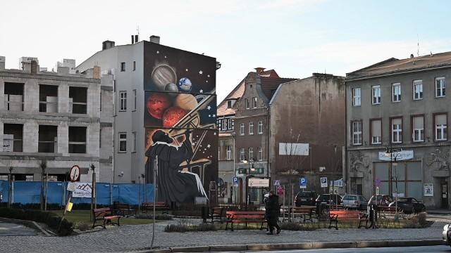 Na jednej ze ścian kamienicy przy żagańskim rynku, tuż obok zabytkowego ratusza powstał ogromny mural z wizerunkiem Johannesa Keplera. To już drugi w ostatnich miesiącach mural w centrum Żagania. Pierwszy powstał na ścianie innej kamienicy i przedstawia najważniejsze zabytki miasta w kolorowym kolażu. Autorami astronomicznego muralu z wizerunkiem jednego z ważniejszych ludzi niegdyś żyjących i pracujących w Żaganiu, którym bez wątpienia jest Johannes Kepler, są dwaj młodzi artyści: Łukasz Gierlak i Artur Marciniszyn z K85 STUDIO. U podnóża ich ogromnego dzieła wisi tablica upamiętniająca fundatorów i instytucje, dzięki którym mógł powstać ten obraz oraz nazwiska samych autorów.Czy i gdzie powstaną w Żaganiu nowe uliczne dzieła i co będą przedstawiać dowiemy się pewnie niebawem, bo te dwa pierwsze żagańskie murale pokazały, że jest społeczna akceptacja i popyt na tego typu sztukę w mieście.Polecamy wideo: Jerzy Kukuczka - nowy mural z wizerunkiem himalaisty powstał w Bogucicach