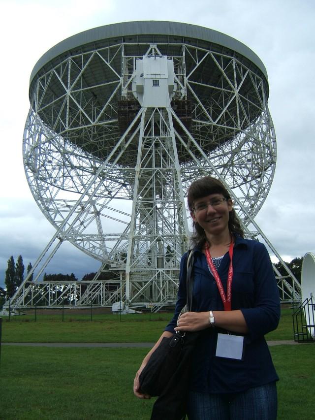 Karolina Rożko pozuje na tle radioteleskopu w Obserwatorium Jodrell Bank w Anglii