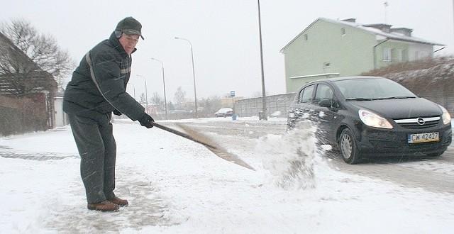 Ryszard Biegalski odśnieża chodnik przy ulicy Robotniczej