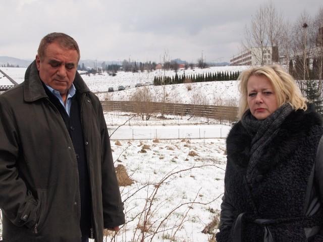 Małgorzata Fredrik i Lesław Mikołajski na tle działek (tam, gdzie rząd krzewów w oddali), na których miały powstać nowe groby. Mieszkańcy protestowali przeciwko planom. Ostatecznie wygrali.