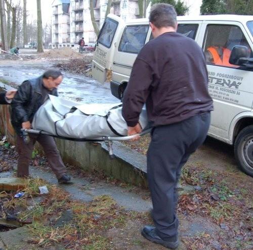 Policja i firma pogrzebowa zabiera zwłoki ofiary wypadku.