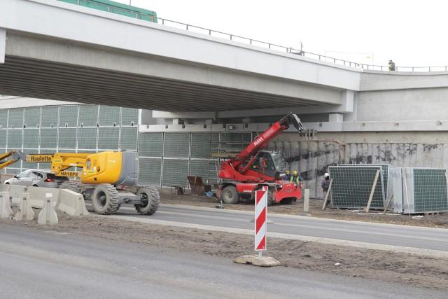 Przebudowa DK 94 w Sosnowcu: Pracownicy montują na ścianach wykopu ekrany dźwiękochłonne, trwają prace na skarpach, oraz infrastrukturze obok jezdniZobacz kolejne zdjęcia. Przesuwaj zdjęcia w prawo - naciśnij strzałkę lub przycisk NASTĘPNE