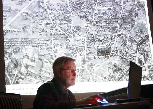 Zygmunt Walkowski na tle jednego z niemieckich zdjęć lotniczych Białegostoku. Tuż nad laptopem widoczna charakterystyczna bryła kościoła św. Rocha, a idąc nieco w lewo widzimy dużą kępę drzew u wylotu ulicy Krakowskiej – czyli wzgórze Magdaleny.