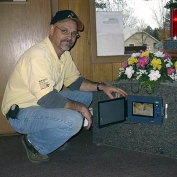 Cmentarny telewizor przymocowuje się do pomnika. Działa na baterie, jest odporny na wszelkie warunki atmosferyczne.
