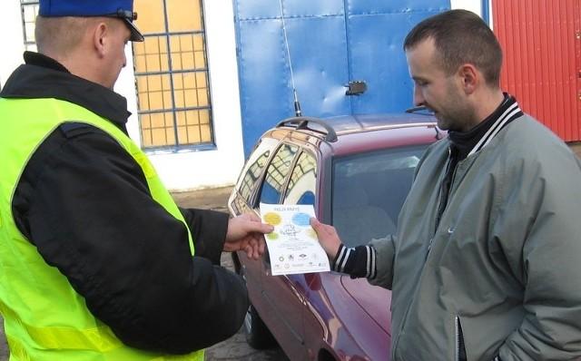 Policjanci z Człuchowa wręczają kierowcą edukacyjne ulotki.