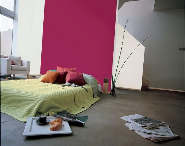Zielona kapa i kolorowe poduszki na łóżku w sypialniNarzuta w kolorze limonki uspokaja i subtelnie skłania do romantycznych uniesień. A poduszki w ciepłych barwach takich jak czerwienie i pomarańcze pomogą uzyskać efekt spowitej kwiatami wiosennej łąki. To poprawi nam humor w deszczowe i zimne dni.