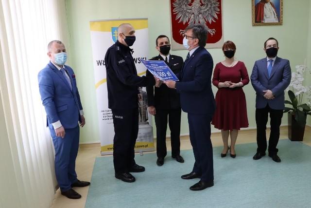 Starosta włoszczowski Dariusz Czechowski wręcza pamiątkowy bon pierwszemu zastępcy komendanta powiatowego policji we Włoszczowie nadkomisarzowi Markowi Gajowi.